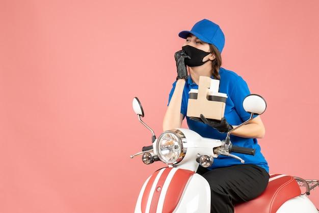 パステル調の桃の背景に注文を配達するスクーターに座って医療用マスクと手袋をはめた思慮深い女性配達員の正面図