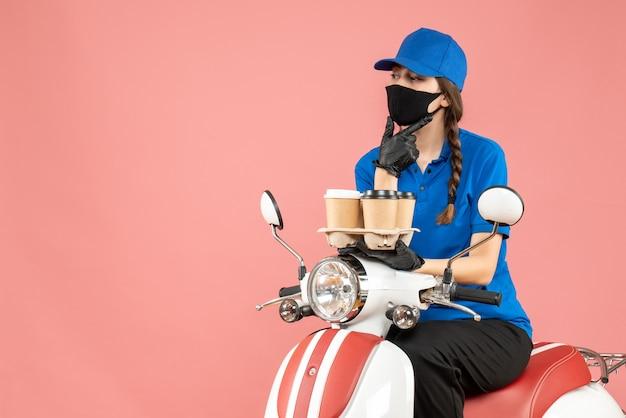 パステルピーチの背景に注文を保持しているスクーターに座っている医療用マスクと手袋を身に着けている思いやりのある女性の配達人の正面