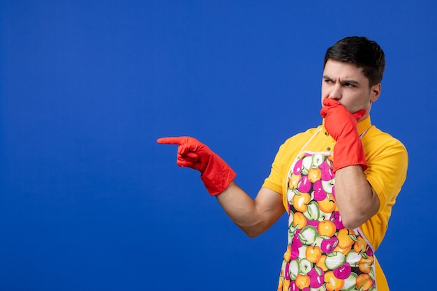 青い壁に立ったまま指で指しているエプロンの思いやりのある男性の家政婦の正面図