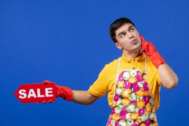 파란색 벽에 판매 표지판을 들고 있는 노란색 티셔츠를 입은 사려깊은 남성 가사도우미의 전면