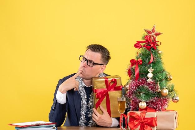 Вид спереди вдумчивого человека, положившего палец на рот, сидя за столом возле рождественской елки и подарков на желтом