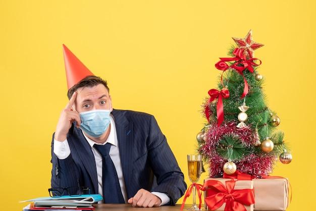 クリスマスツリーの近くのテーブルに座っているパーティーキャップと黄色のプレゼントと思いやりのある男の正面図