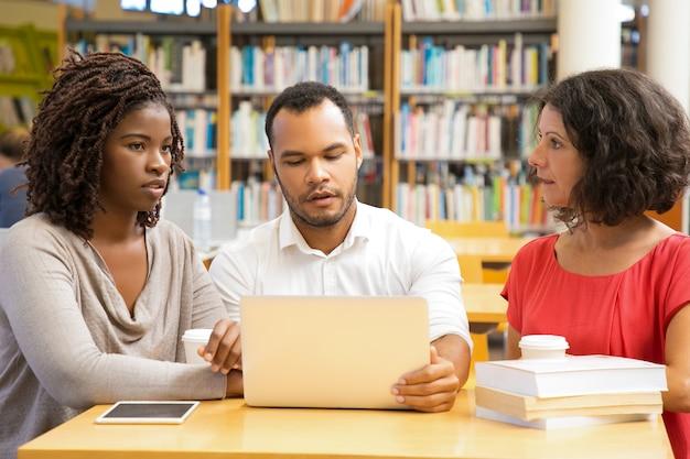 Вид спереди вдумчивых людей, работающих в библиотеке
