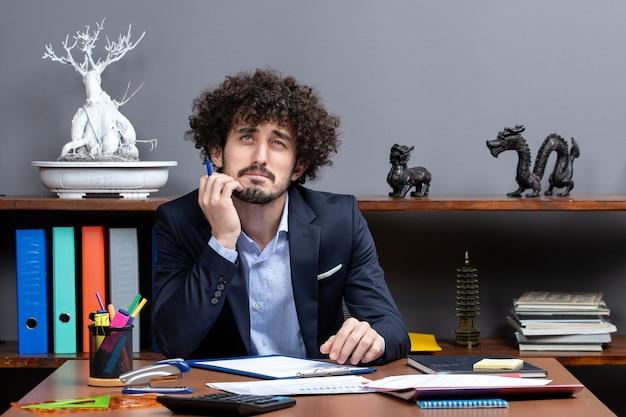 현대 사무실에서 책상에 앉아 사려 깊은 젊은 사업가의 전면보기