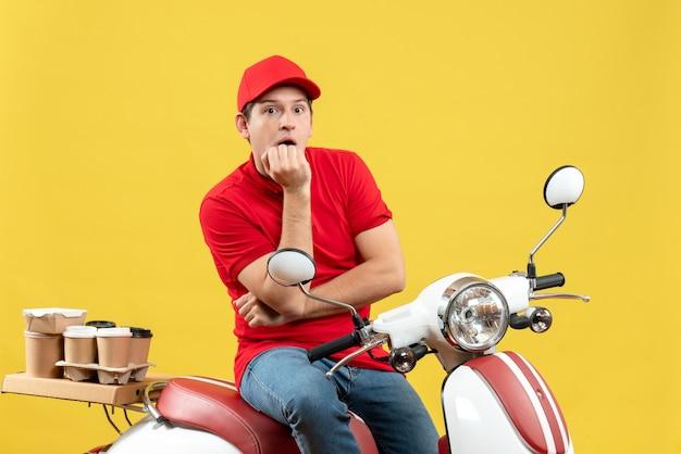 黄色の背景に注文を配信赤いブラウスと帽子を身に着けている思いやりのある若い男の正面図