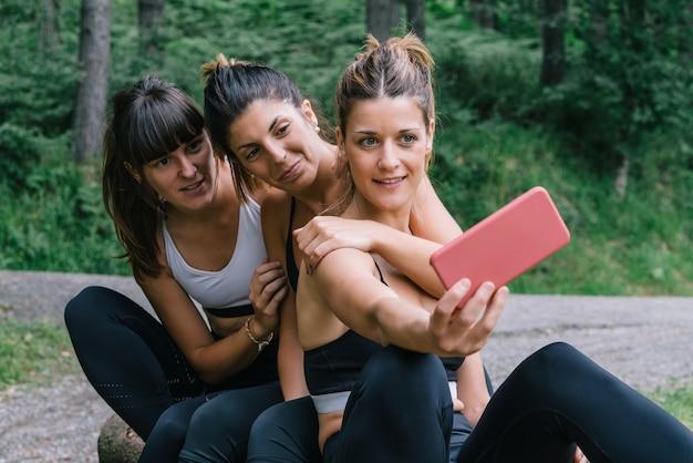 Вид спереди трех красивых счастливых спортсменок, делающих селфи на видео или фото после гонки в зеленом лесу