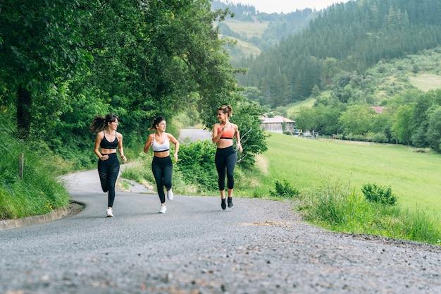 Вид спереди трех красивых счастливых женщин, бегущих по дороге через красивый зеленый лес с множеством деревьев