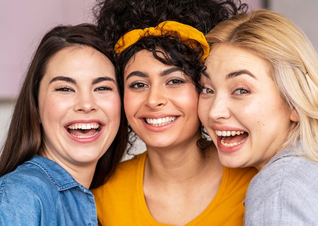 一緒にポーズと笑顔の3人の幸せな女性の正面図