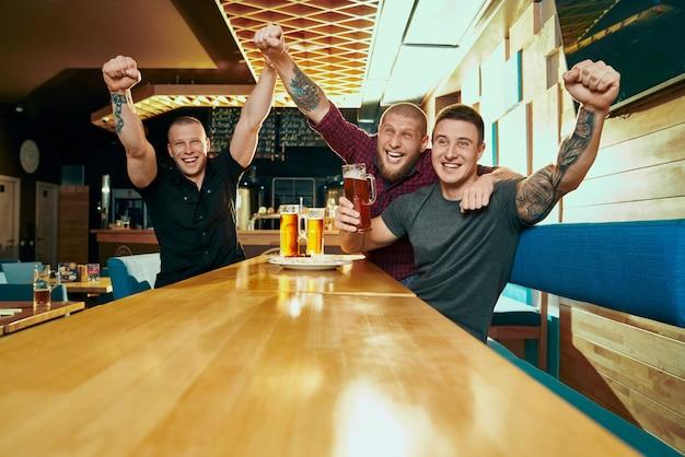 축구를보고 응원하고 주말에 술집에서 쉬는 세 명의 남성 팬의 전면 모습. 테이블에 앉아 맥주를 마시고 바에서 웃고 쾌활한 남자. 행복과 여가의 개념.