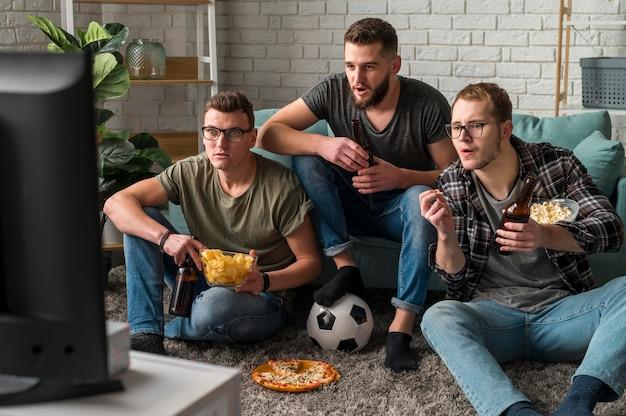 간식과 맥주를 마시면서 함께 tv에서 스포츠를 시청하는 세 남자 친구의 전면보기