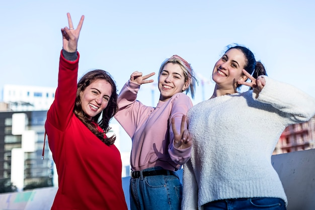 Вид спереди трех молодых девочек-подростков, делающих знак мира на открытом воздухе в солнечный день