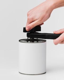 空白のラベルとオープナーを使用して手で缶の正面図