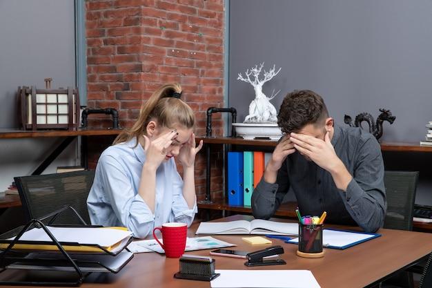 사무실 환경에서 테이블에 앉아 피곤한 젊은 여성 노동자와 그녀의 남성 동료의 전면 보기
