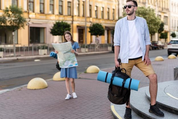 Вид спереди туристической пары, держащей карту и рюкзак