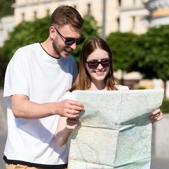 Вид спереди туристической пары, глядя на карту