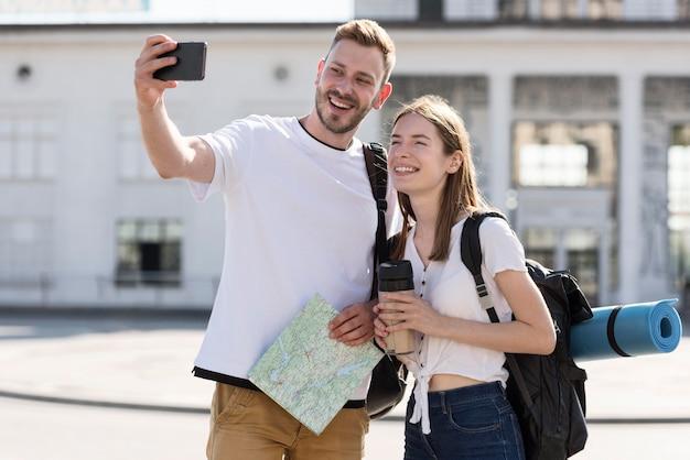 Selfieを取ってバックパックと屋外観光カップルの正面図