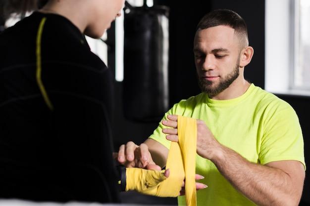 練習の準備で女性ボクサーの手を包むトレーナーの正面図