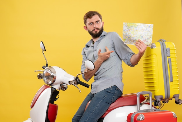 黄色の誰かを保持しているスーツケースを持ってバイクに座っている混乱した若い男と旅行の概念の正面図