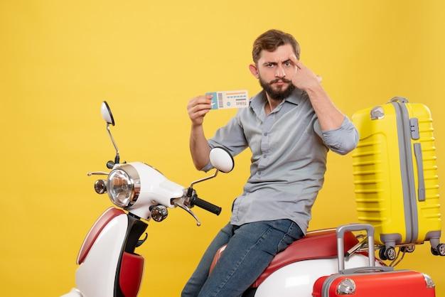 黄色のチケットを保持しているスーツケースを持ってオートバイに座っている不思議な考えの若い男と旅行コンセプトの正面