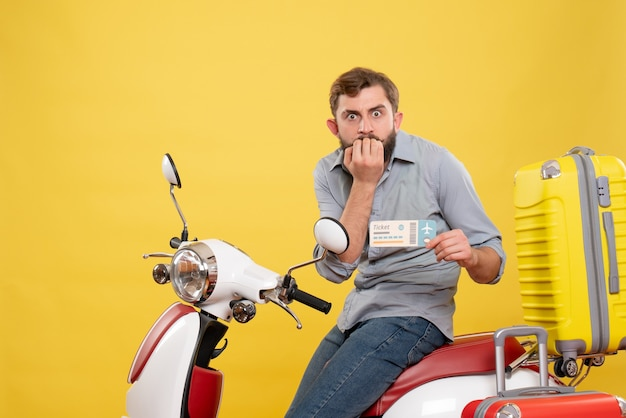 黄色のチケットを保持しているスーツケースを持ってバイクに座っている不思議な若い男と旅行の概念の正面図