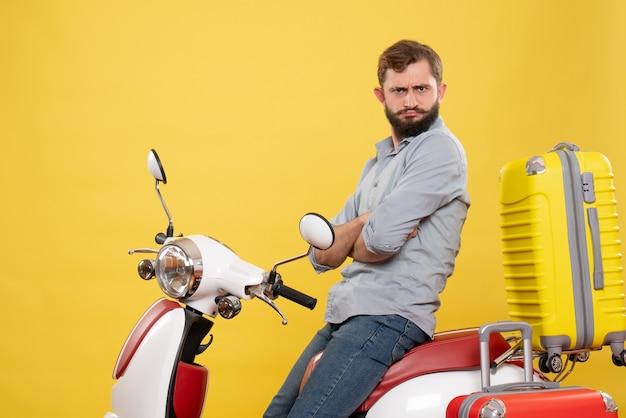 黄色のスーツケースを持ってバイクに座っている不思議な若い男と旅行の概念の正面図