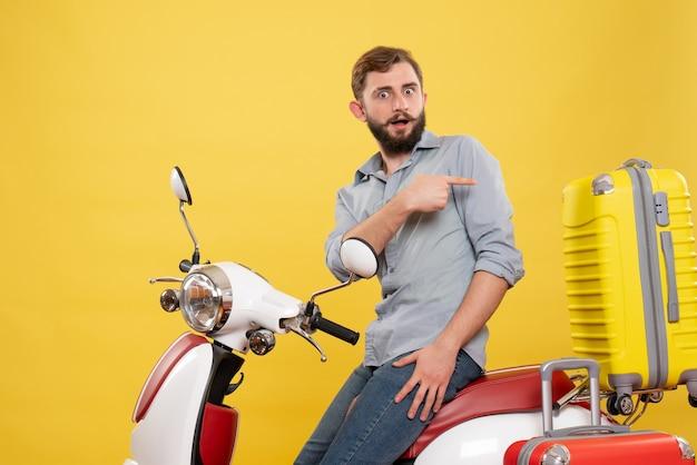 가방이 노란색에 다시 가리키는 motocycle에 앉아 궁금해하는 젊은 남자와 여행 개념의 전면보기