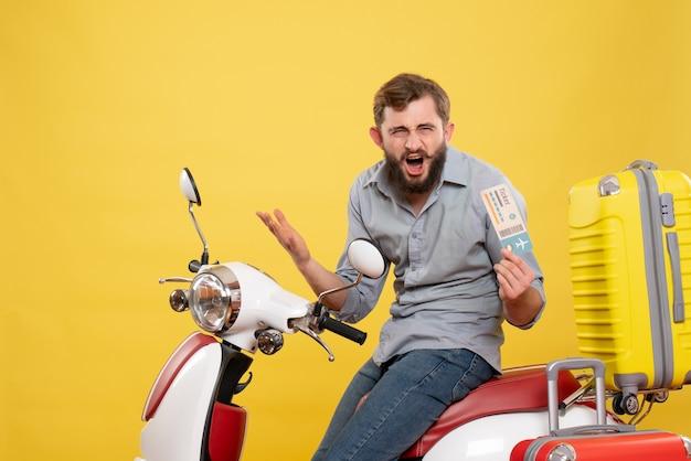 黄色のチケットを保持しているスーツケースを持ってバイクに座っている心配している若い男と旅行の概念の正面図