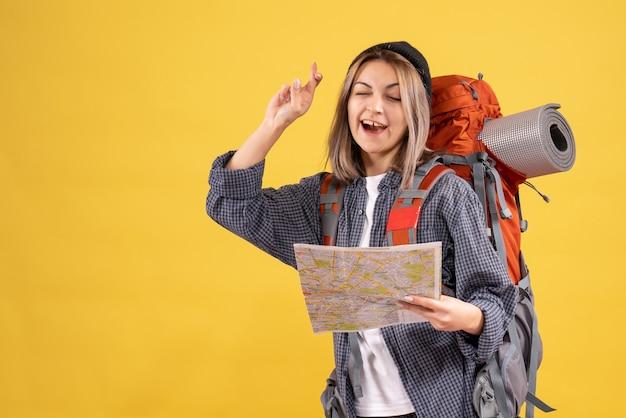 Вид спереди путешественницы с рюкзаком, держащей карту, делающую знак желания