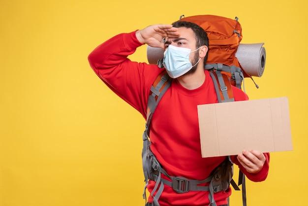 黄色い背景に何かを注意深く見て、書くことなくシートを見せるバックパック付きの医療用マスクを着た旅行者の男性の正面図