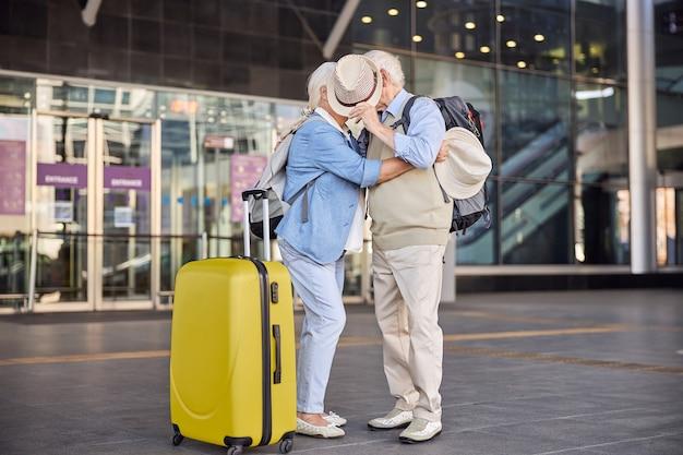 공항 건물 앞에서 키스하는 사랑에 빠진 두 노인의 전면보기