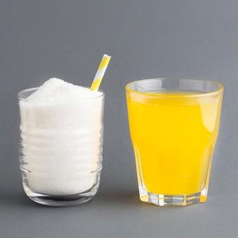 Вид спереди двух стаканов с безалкогольным напитком и сахаром
