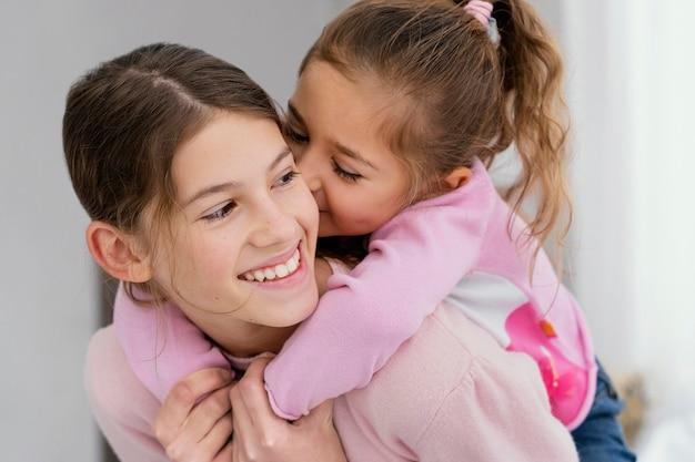 집에서 함께 두 명의 작은 웃는 자매의 전면보기 프리미엄 사진