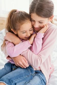 家で一緒に遊んでいる2人の笑顔の姉妹の正面図 Premium写真