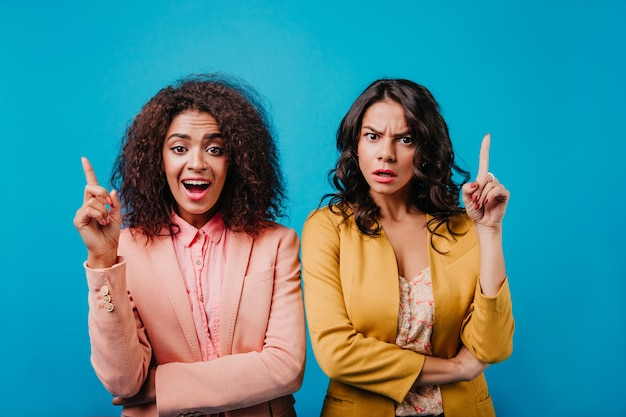 파란색 벽에 감정을 표현하는 두 젊은 여성의 전면보기