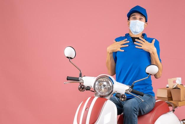 パステル調の桃の背景に注文を配達するスクーターに座っている帽子をかぶった医療マスクを着た不確かな宅配便の男性の正面図