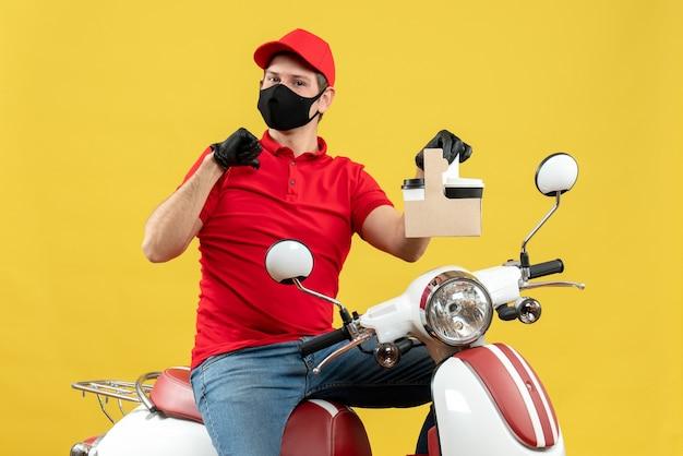医療用マスクに赤いブラウスと帽子の手袋を着用してスクーターに座っている不確かな宅配便の男性の正面図