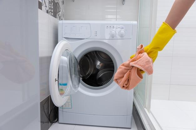 小さなフロントローディング洗濯機の前に汚れたピンクのタオルを持っている識別できない黄色のゴム手袋をはめた手の正面図