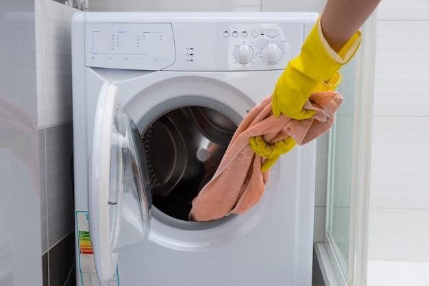 小さなフロントローディング洗濯機からピンクのタオルを引っ張る識別できない黄色のゴム手袋をはめた手の正面図