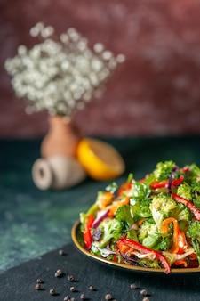 プレートに新鮮な食材と黒のまな板にコショウを入れたビーガンサラダの正面図