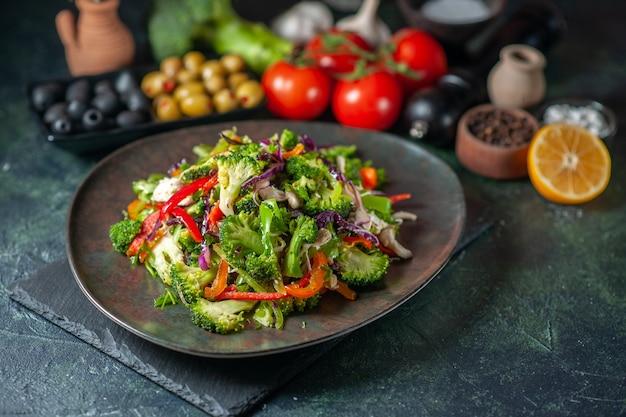 暗い背景の上の黒いまな板にさまざまな材料とフォークの野菜サラダの正面図