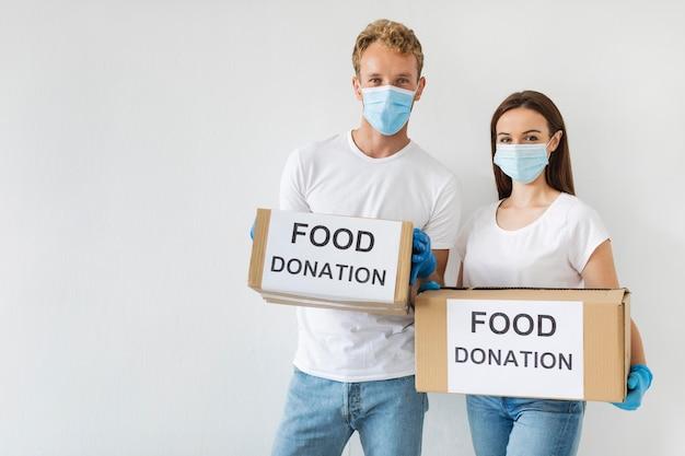 Вид спереди добровольцев, держащих коробки для пожертвований с копией пространства