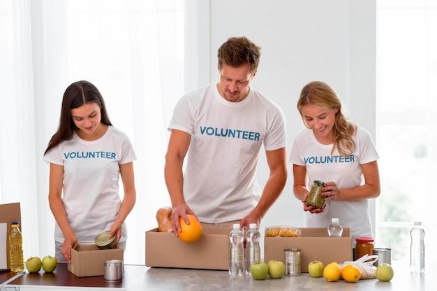 Вид спереди добровольцев, упаковывающих коробки с продовольственными пожертвованиями
