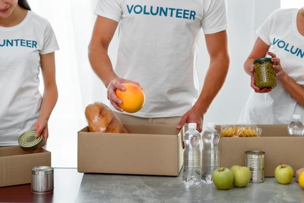 Вид спереди добровольцев, упаковывающих коробки с едой