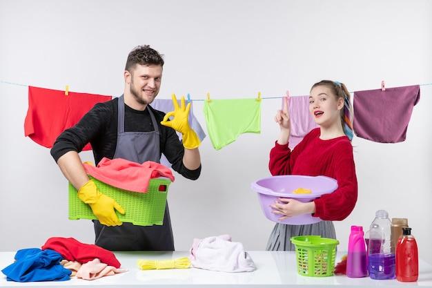 Вид спереди человека времени стирки, делающего знак ок, и его жена, стоящая за столом, корзины для белья и стиральные машины на столе
