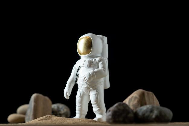 달에 돌을 가진 백색 우주 비행사의 전면보기