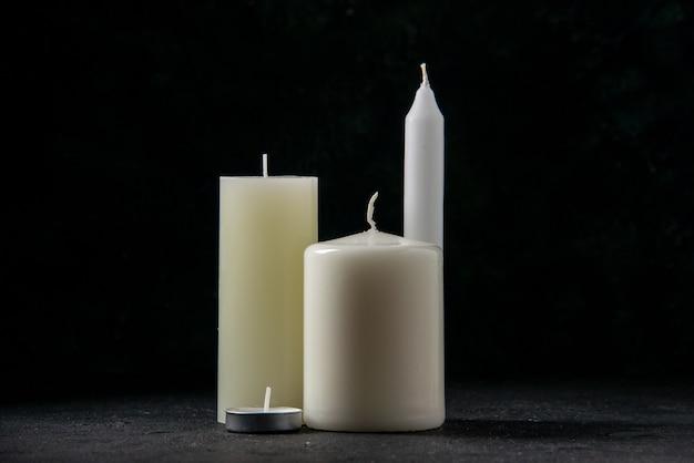Вид спереди белых свечей на черном