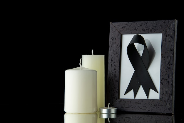 黒い壁に額縁が付いた白いキャンドルの正面図