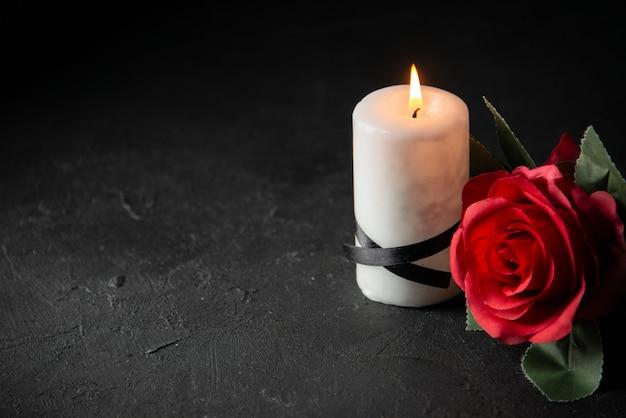 어두운 벽에 붉은 꽃과 하얀 촛불의 전면보기