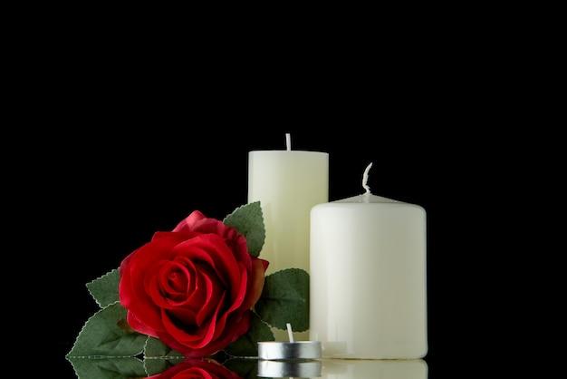 검은 벽에 붉은 꽃과 흰색 촛불의 전면보기