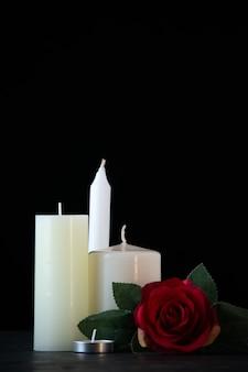 Вид спереди белых свечей с красной розой как память на темной стене